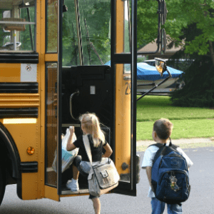 young children getting on a school bus